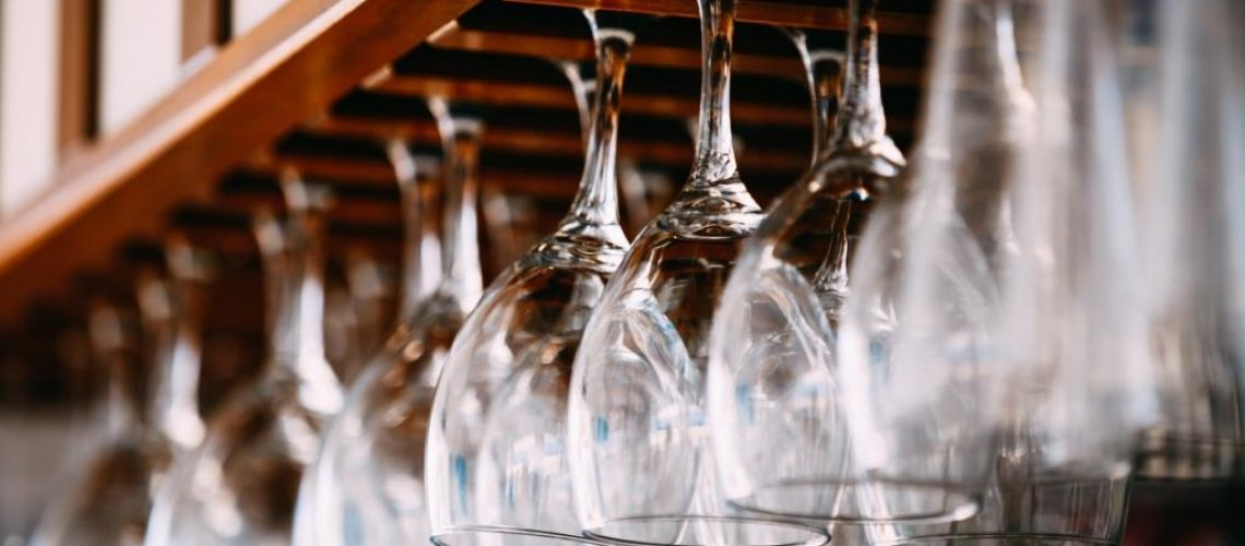empty-glasses-for-wine-above-a-bar-rack-hanging-PMWRAPK